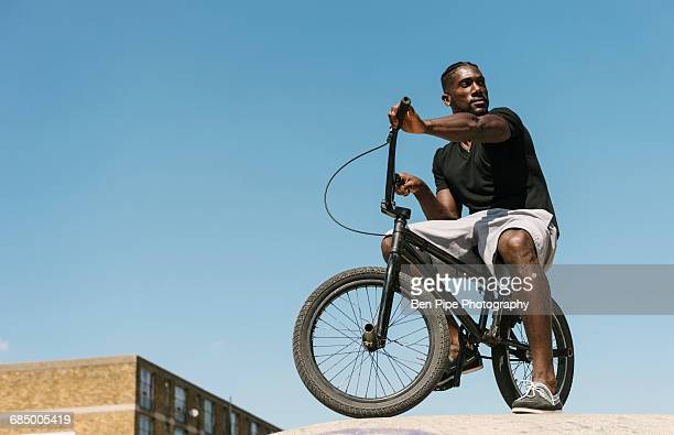 young man on bmx bicycle looking over his shoulder in skatepark - brixton stock pictures, royalty-free photos & images