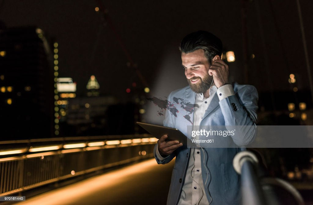 Young man on bridge at night with world map emerging from tablet : Foto de stock