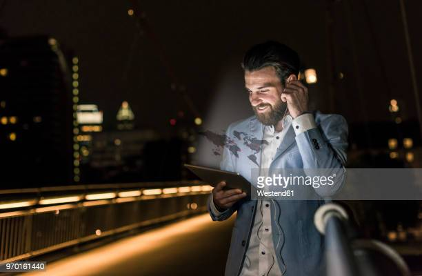 young man on bridge at night with world map emerging from tablet - caucasian appearance stock pictures, royalty-free photos & images