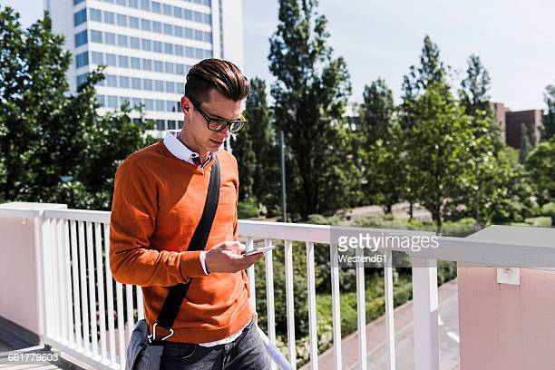 young man on bridge looking at cell phone - crossbody bag photos et images de collection