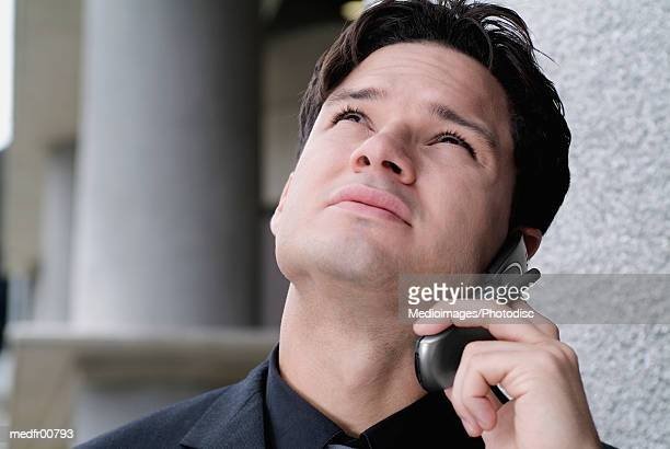 Young man on cell phone and looking up, close-up