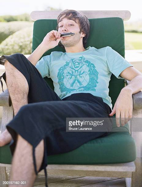 Young man on chair with harmonica in mouth, portrait