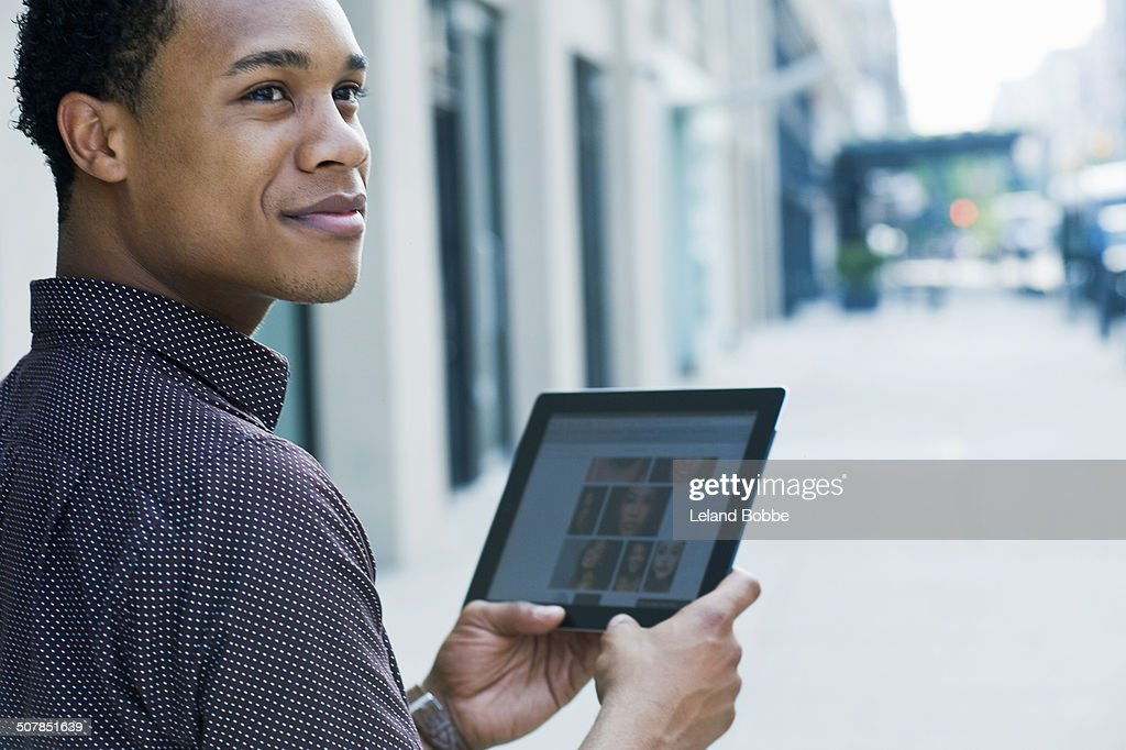 Young man on city street using digital tablet and looking over shoulder : Stock Photo