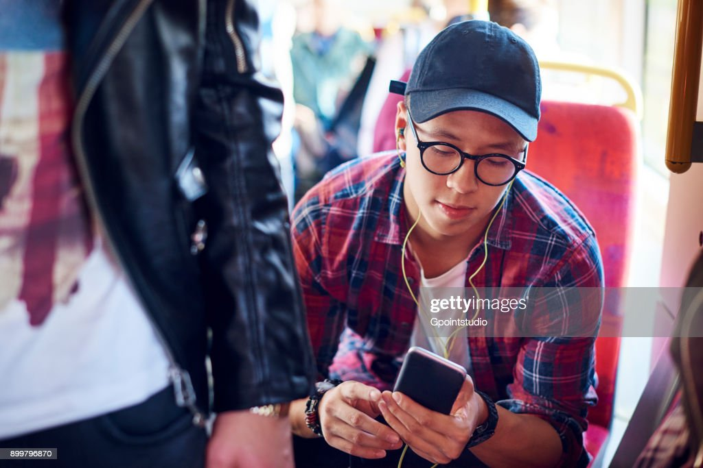 Young man on city tram looking at smartphone and listening to earphones : Stock-Foto