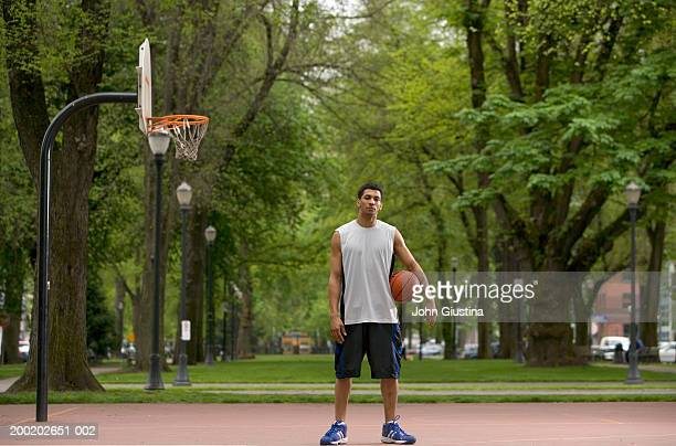 Young man on court with basketball, portrait