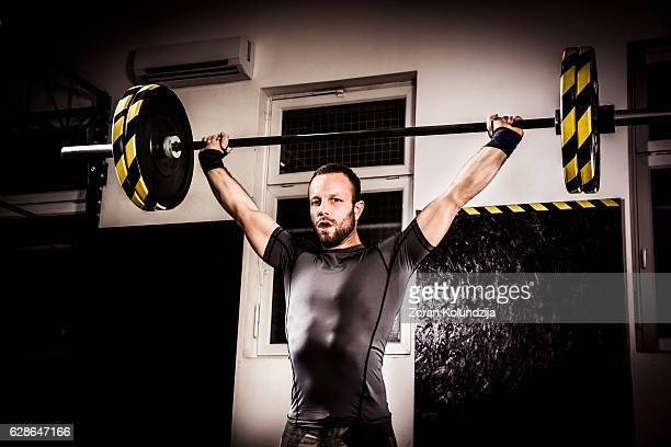 Young man on cross training lifting weights