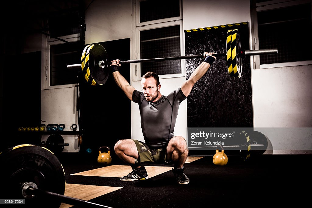 Young man on cross training lifting weights : ストックフォト