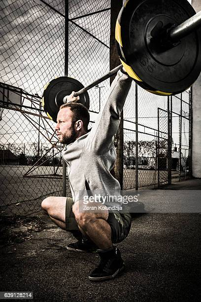 young man on cross training lifting weights - snatch weightlifting stock photos and pictures