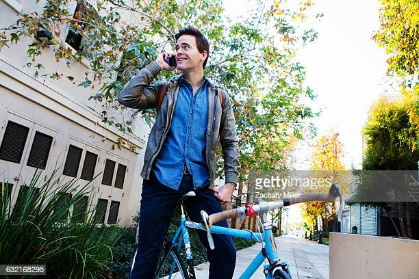 young man on cycle chatting on smartphone - monrovia california stock pictures, royalty-free photos & images