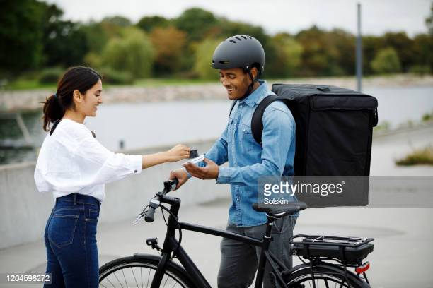 young man on electric bike with food delivery backpack getting contactless payment - charging sports stock pictures, royalty-free photos & images