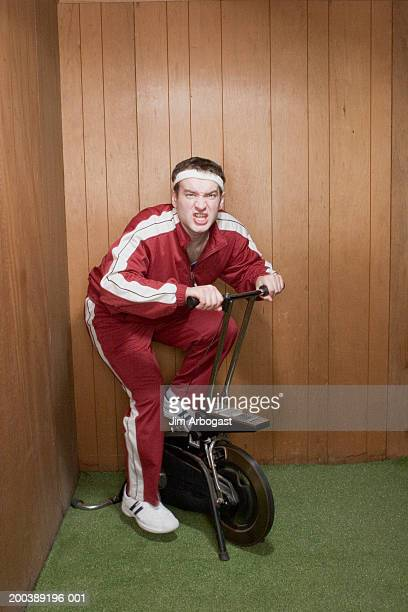 Young man on exercise bike, grimacing, portrait
