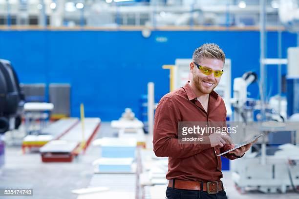 若い男性の工場 shopfloor デジタルタブレットを使用して、