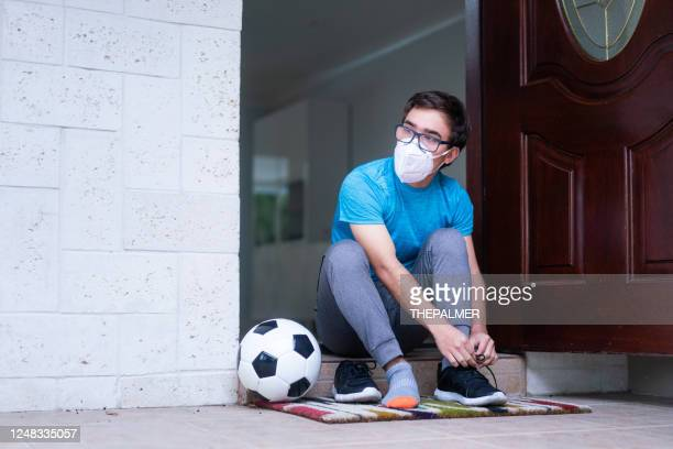 young man on front door with putting on sport shoes - football face mask stock pictures, royalty-free photos & images