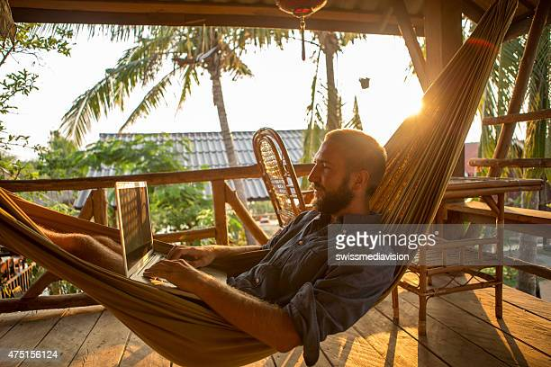 Young man on hammock at sunset working on computer