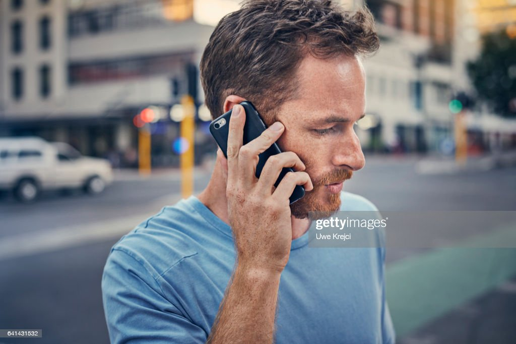 Young man on his phone in the city : Foto stock