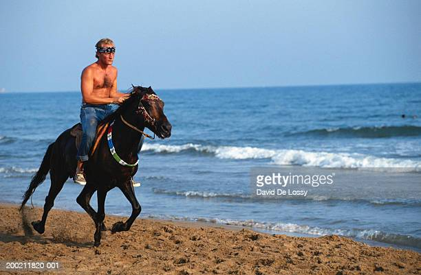 Young man on horseback, at beach