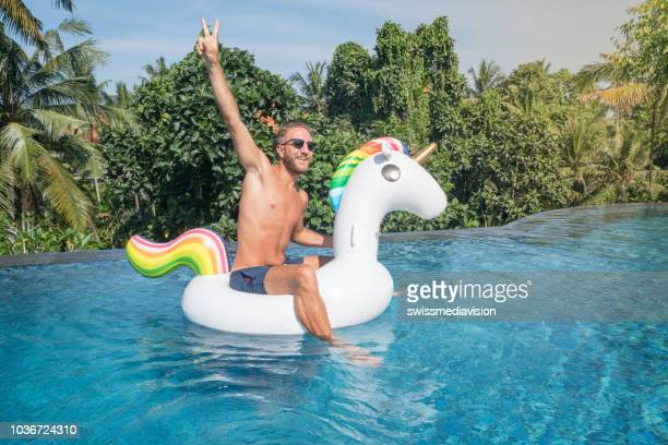 young man on inflatable unicorn having fun in hotel swimming pool, sitting on inflatable toy arms outstretched for freedom and positivity  people travel vacations concept - unicorn stock pictures, royalty-free photos & images