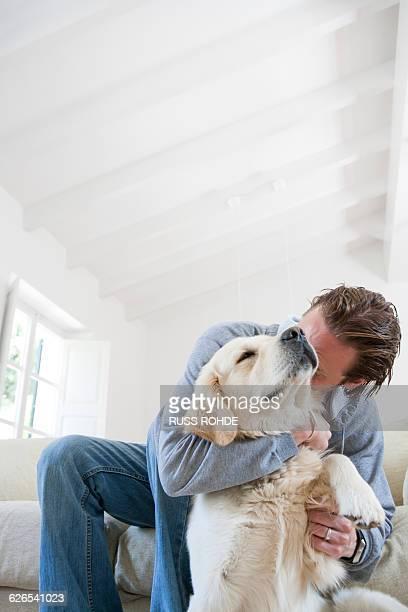 young man on living room sofa hugging golden retriever dog - golden retriever fotografías e imágenes de stock