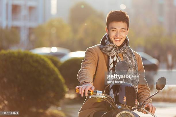 young man on motorcycle in modern city