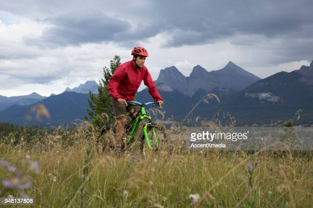 young man on mountain bike rides across meadow - red coat stock pictures, royalty-free photos & images
