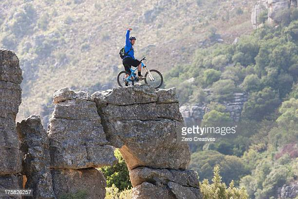 Young man on mountain bike standing on rock formation