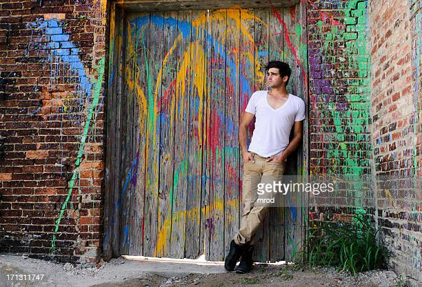 young man on paint-splattered door - v neck stock photos and pictures
