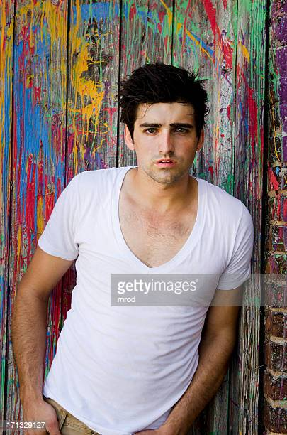 young man on paint-splattered door - v neck stock pictures, royalty-free photos & images