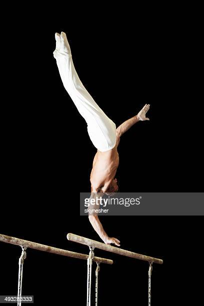 young man on parallel bars. - parallel bars gymnastics equipment stock photos and pictures