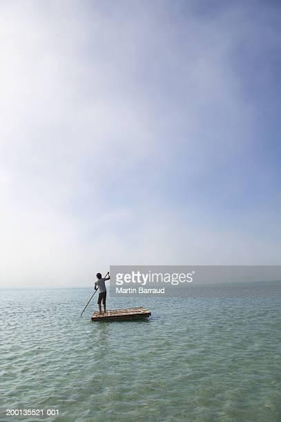 Young man on raft at sea, rear view