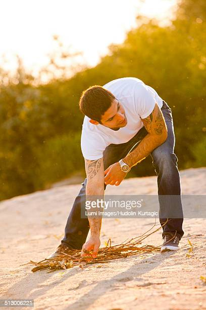 Young man on riverbank gathering firewood, Osijek, Croatia