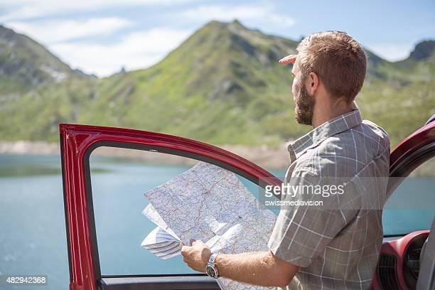 Jeune homme sur un road trip lecture de carte pour les directions
