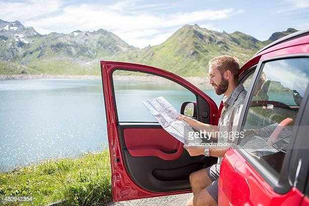 Jeune homme lisant carte de voyage