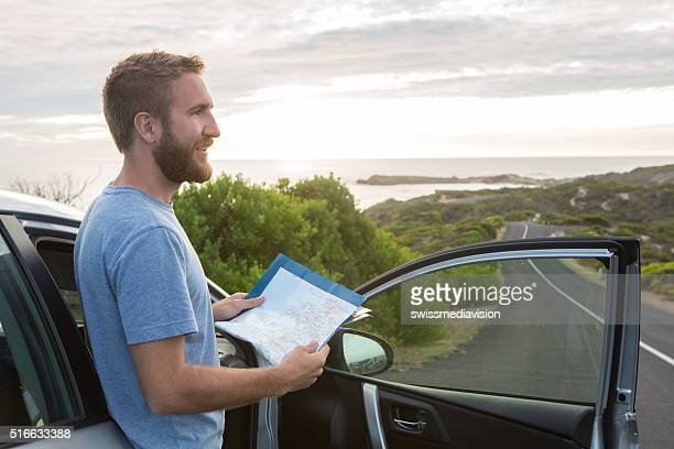 Young man on road trip reads map for directions