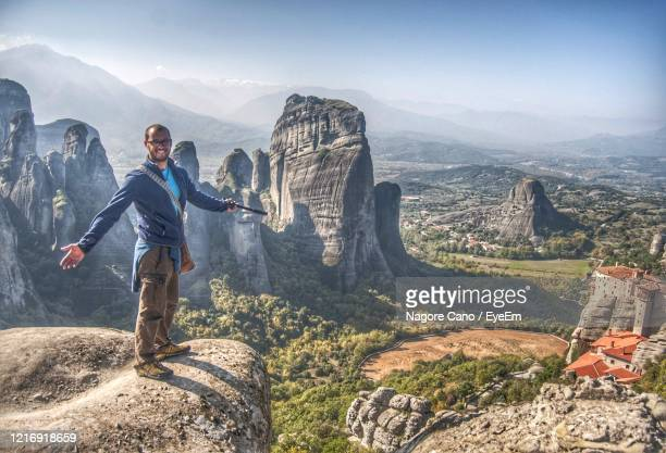 young man on rock against sky in meteora, greece. - greece stock pictures, royalty-free photos & images