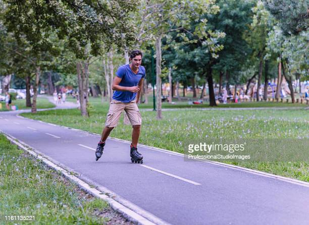 young man on rolling skates in public park - inline skating stock pictures, royalty-free photos & images