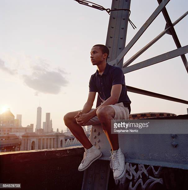 young man on rooftop - 屋根 ストックフォトと画像