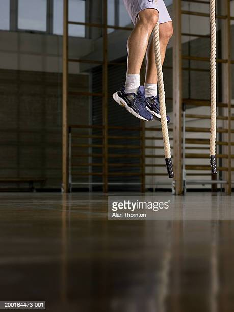 Young man on rope in gymnasium, low section