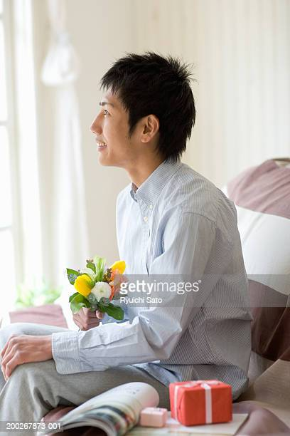 Young man on sofa holding bunch of flowers, smiling, profile
