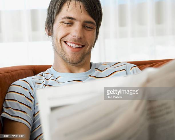 Young man on sofa, reading newspaper, smiling, close-up