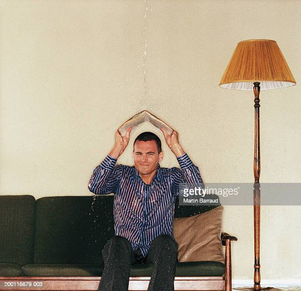 Young man on sofa shielding head from water with open book, portrait