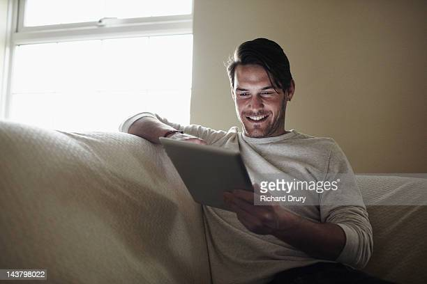 young man on sofa using digital tablet - richard drury stock pictures, royalty-free photos & images