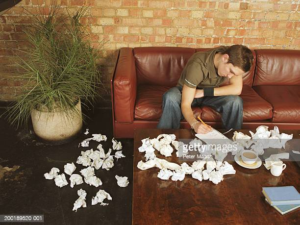 Young man on sofa writing in notebook, surrounded by screwed up paper