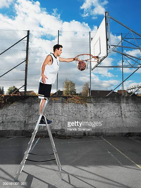 young man on step ladder, dunking basketball in hoop, side view - smooth stock pictures, royalty-free photos & images
