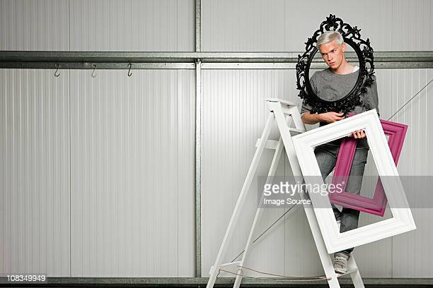 Young man on stepladders carrying picture frames