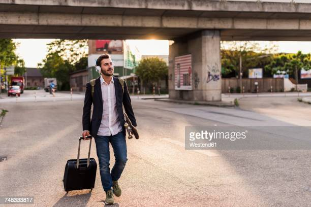 Young man on the move with skateboard, rolling suitcase and headphones