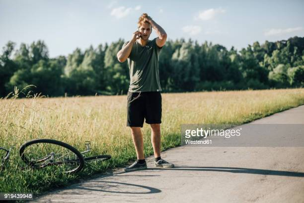 Young man on the phone, bicycle tour, accident