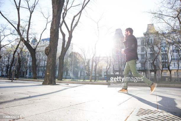 Young man on the phone walking in the city