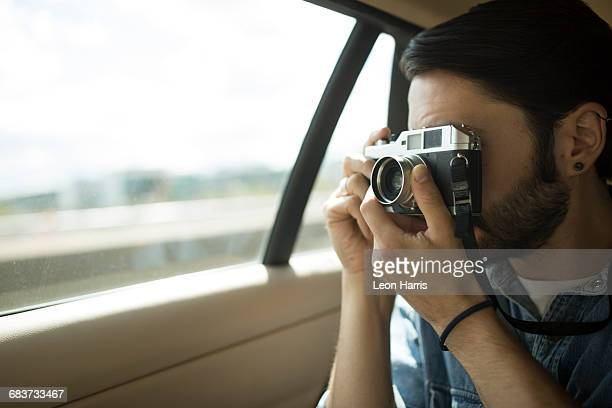 Young man on the road, taking photographs through car window