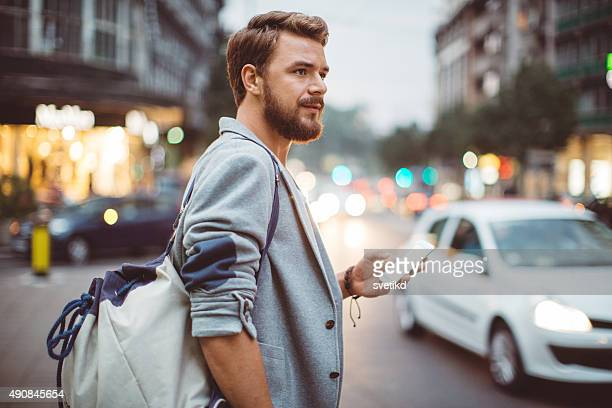 young man on the streets of big city. - looking in bag stock pictures, royalty-free photos & images