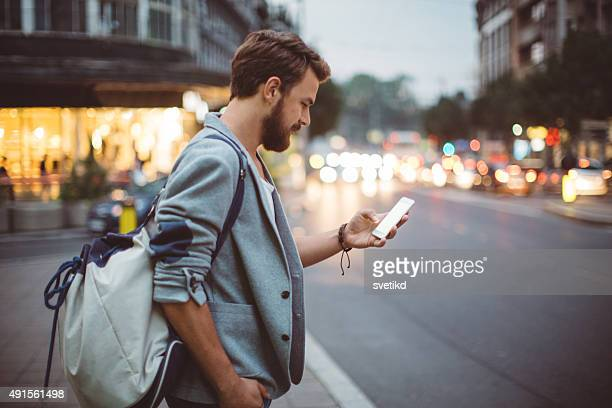 young man on the streets of big city. - hi tech moda stock pictures, royalty-free photos & images
